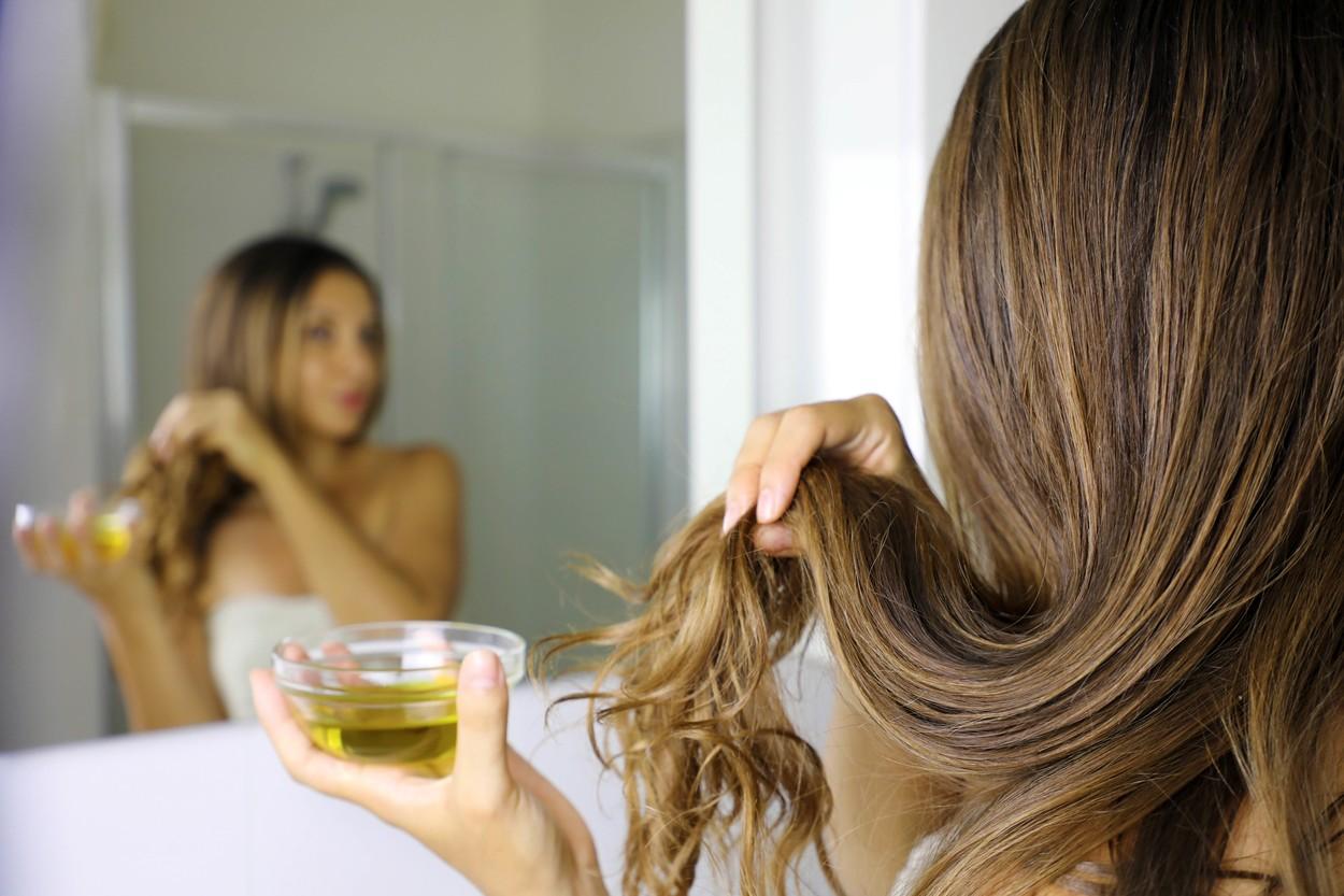 O femeie cu părul lung aplică o mască de păr dintr-un bol în care are ulei de măsline