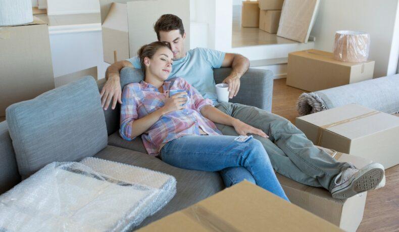 Cuplu care se relaxează pe canapea, înconjurat de multe cutii