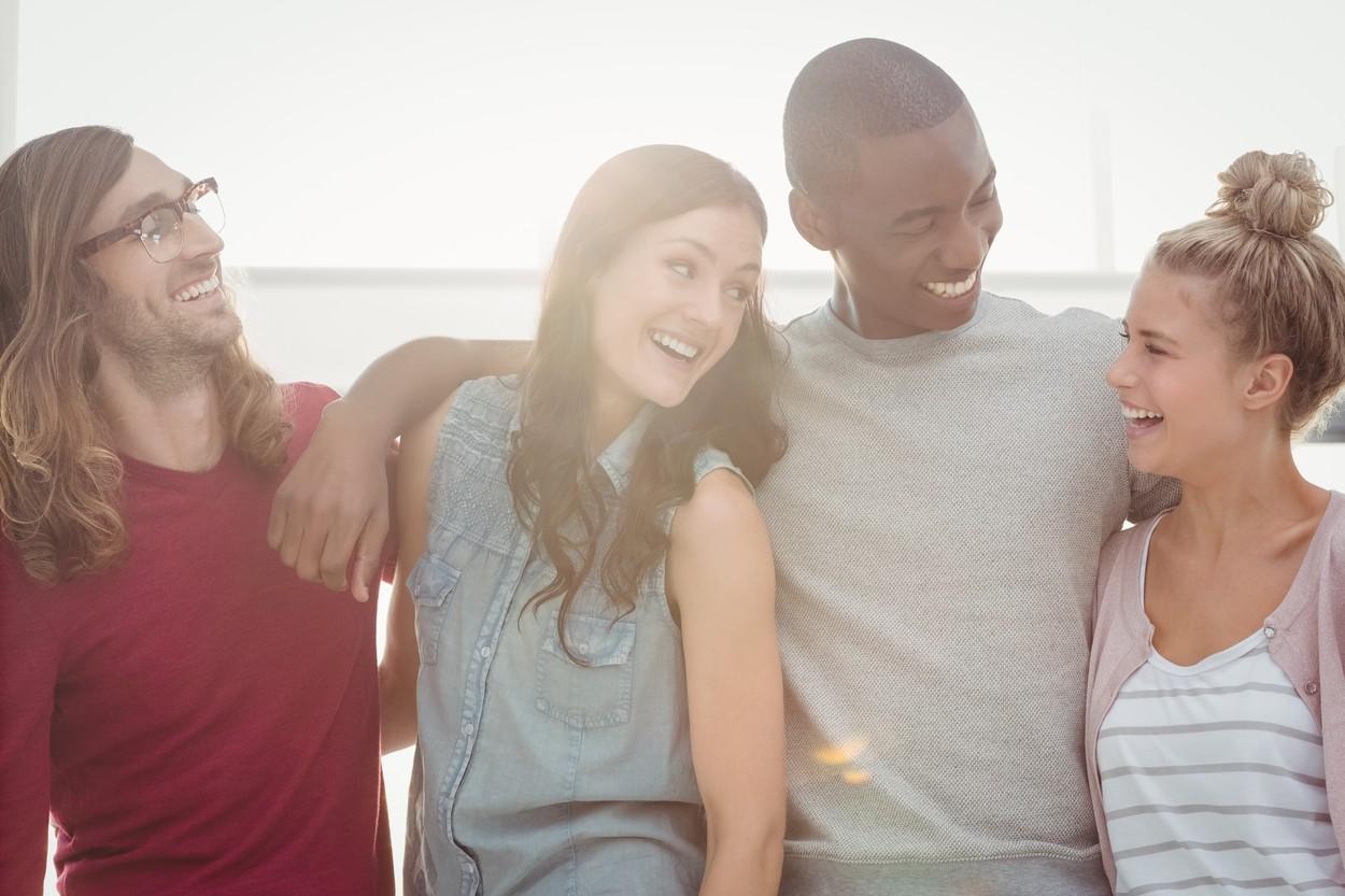 4 prieteni care se îmbrățișează și zâmbesc la malul mării