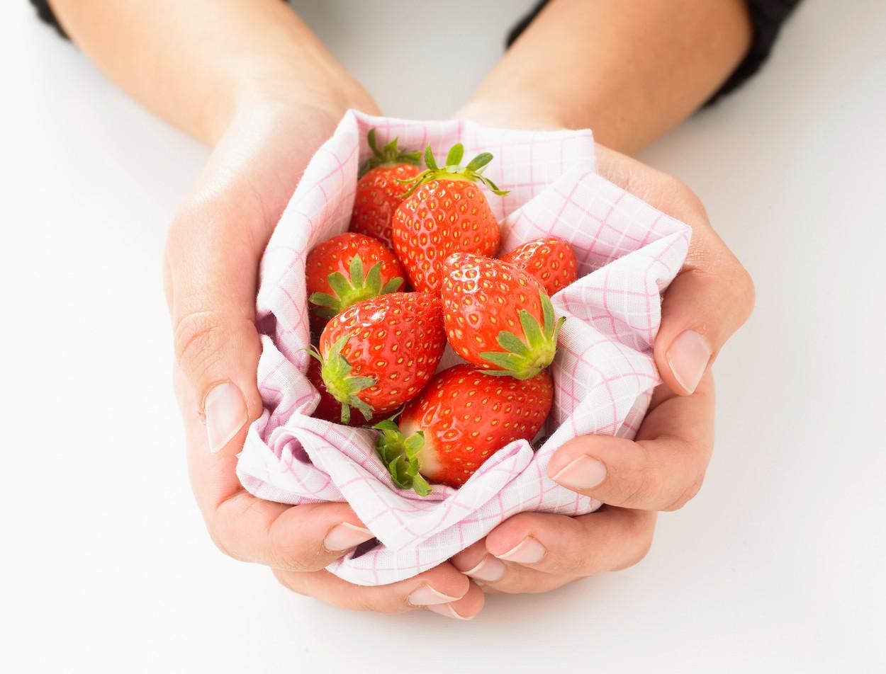 O femeie care ține în palme niște căpșuni