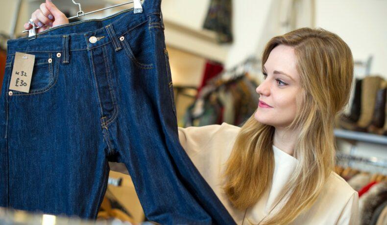 O femeie care își alege o pereche de blugi