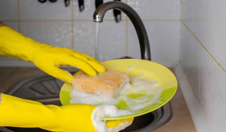 O femeie care spală vasele la chiuvetă