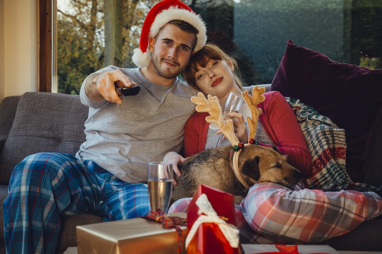 Cuplu care stă pe canapea și se uită la filme de Crăciun