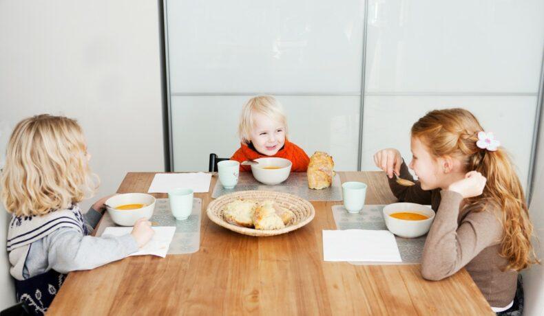Trei copii zâmbitori stau la masa și servesc împreună prânzul