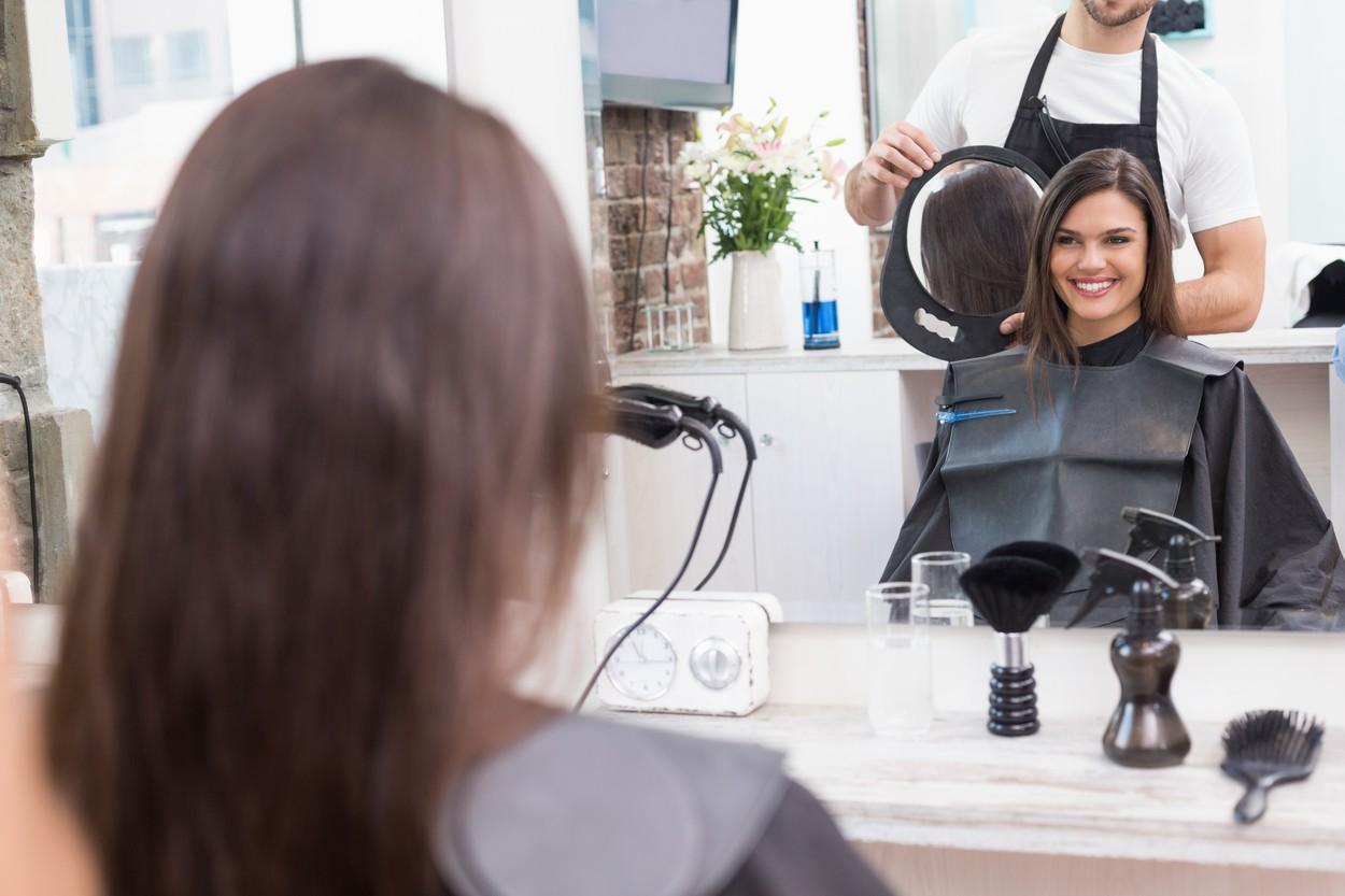 O femeie fericită la salon după tunsoare
