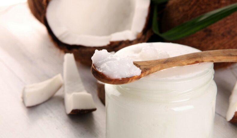 Borcan cu ulei de cocos, a;ezat pe o masă alături de nuci de cocos și frunze de palmier