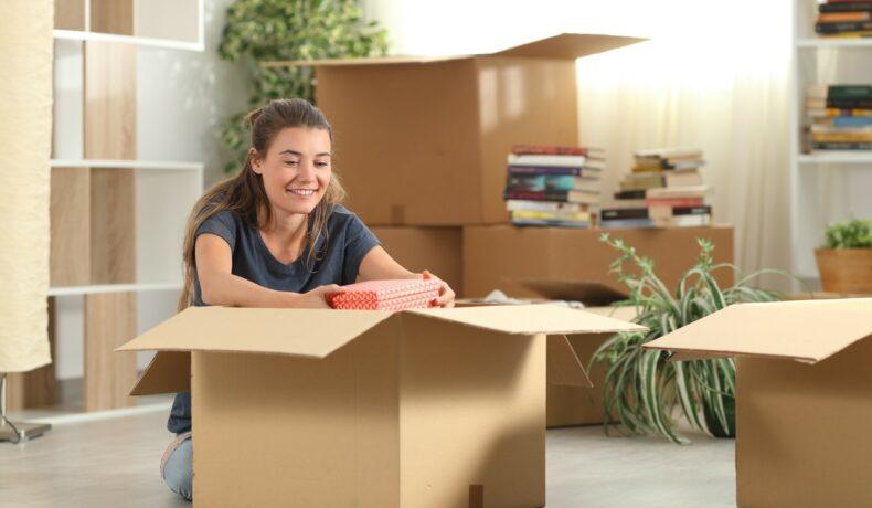 O femeie zâmbește în timp ce despachetează o cutie mare de carton, după ce s-a mutat singură