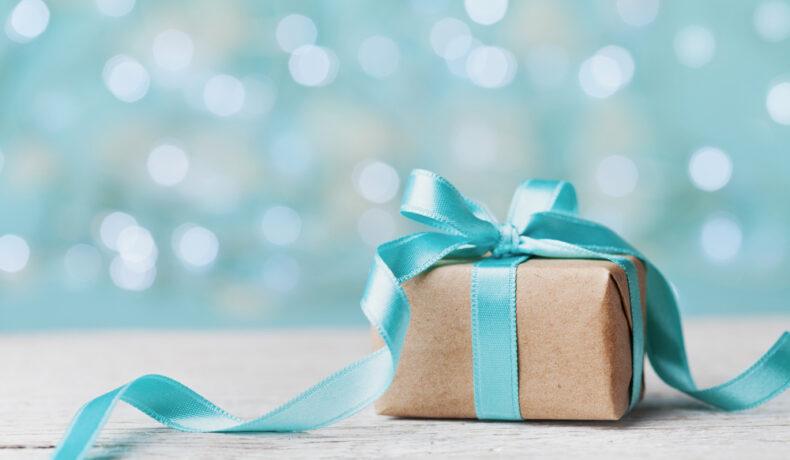 O cutie mică de carton prinsă cu o fundă de culoare albastră
