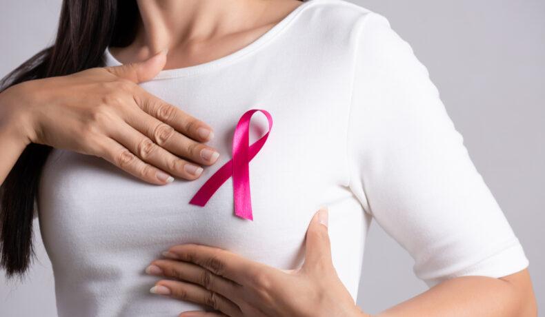 O femeie îmrăcată cu un tricou alb și cu o fundă roz în piept își cuprinde sânul cu ambele mâini
