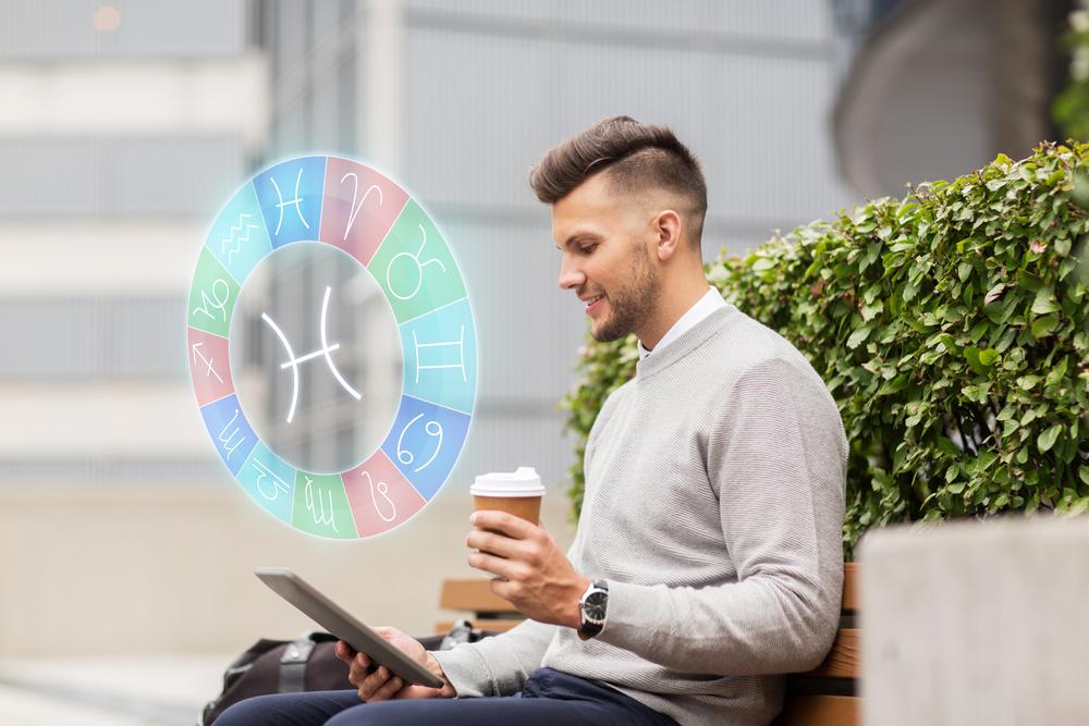 Un bărbat care stă pe o bancă se uită pe tabletă cu un pahar de cafea în mână