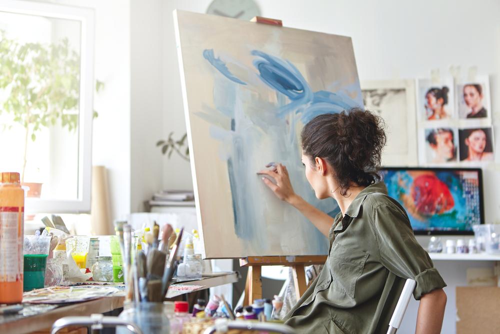 Vedere din spate a unui artist de sex feminin așezat pe scaun în fața unei pânze de pictură și care folosește culorile alb și albastru