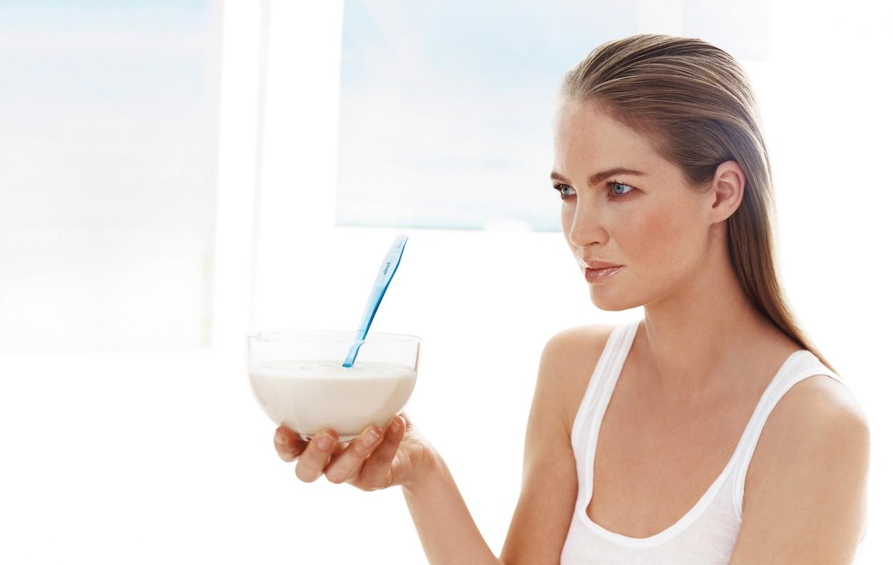 O femeie blondă cu ochi albaștri care ține în mână un bol cu iaurt și privește în zare