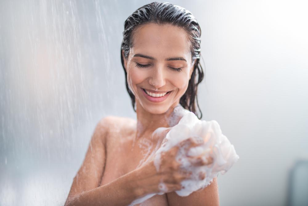 O femeie zâmbitoare care se spală cu un burete plin de spumă