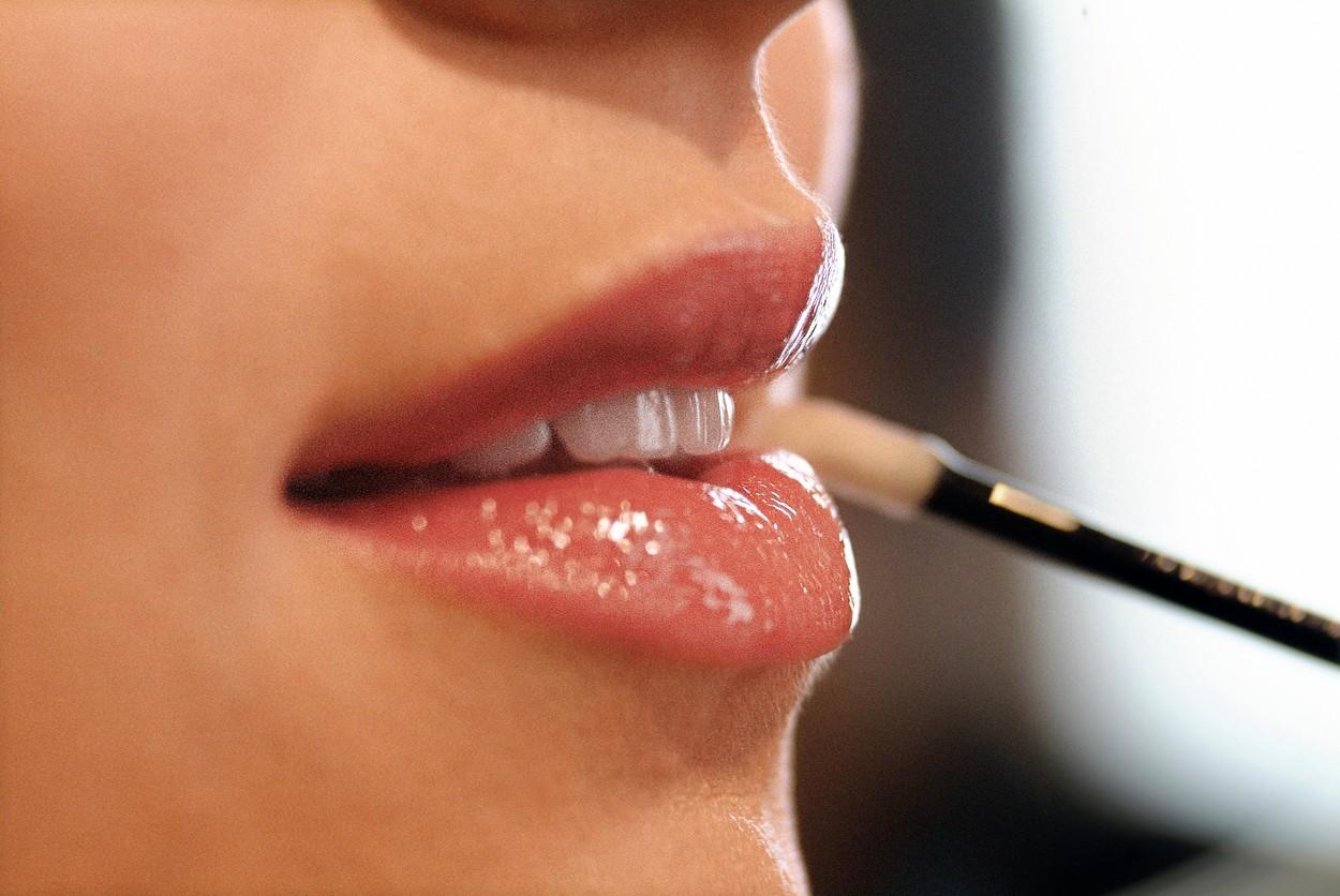 Cadru apropiat cu buzele unei femei, care aplică luciu de buze cu pensula