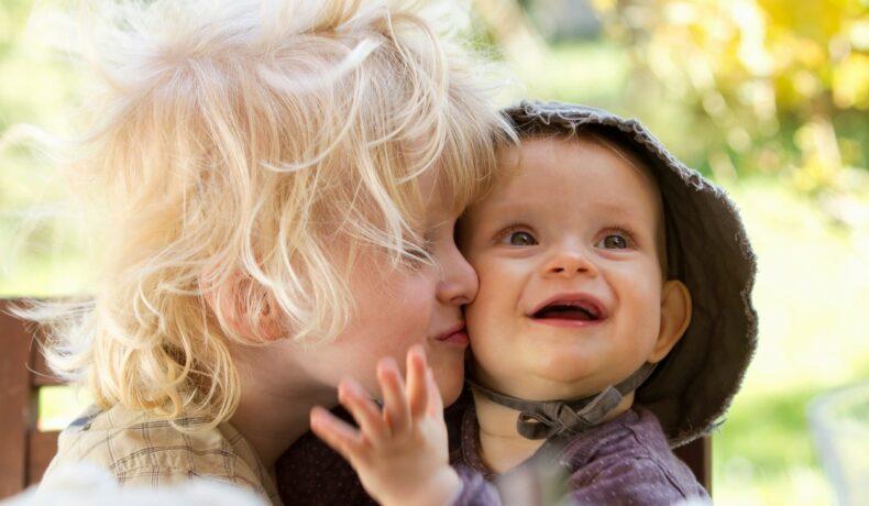 Un copil blond cu plete sărută pe obraz un bebelus zâmbitor cu pălărie