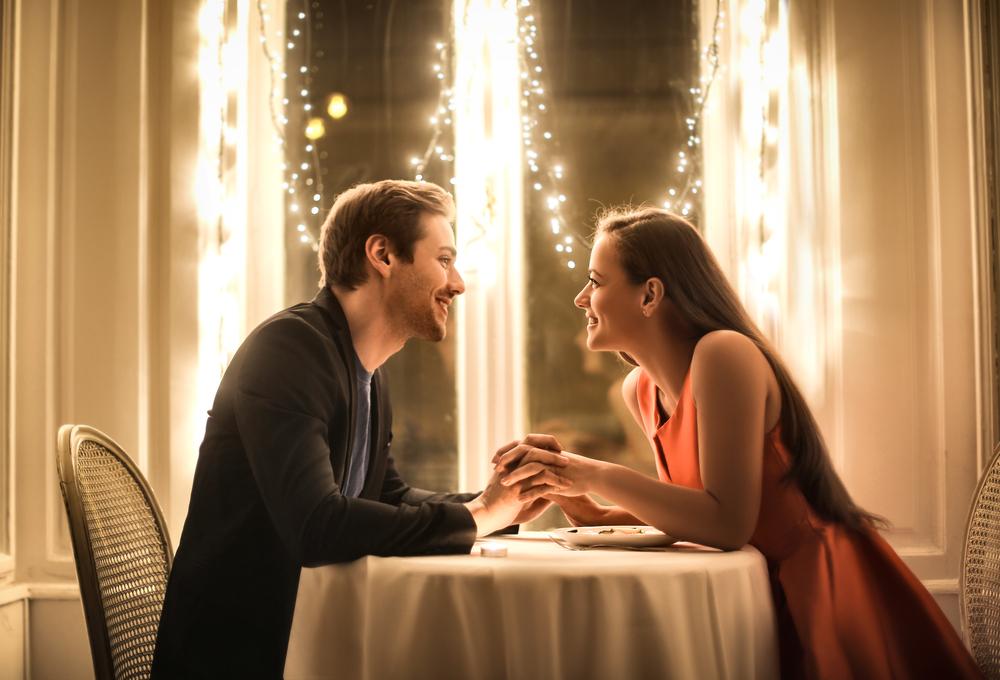 Un bărbat și o femeie stau la masa și se țin de mână