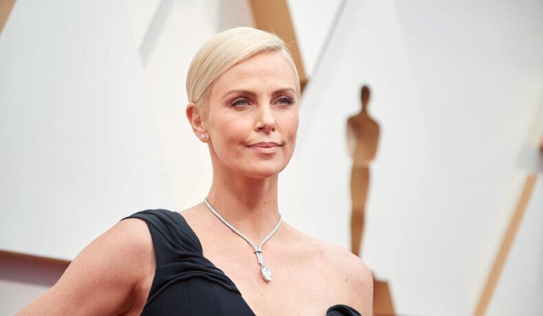 Charlize Theron pozează pe covorul rosu la Premiile Oscar îmbrăcată într-o rochie neagră cu umărul gol