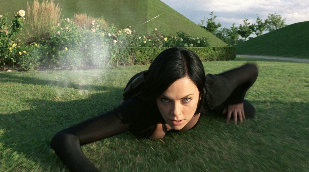 Charlize Theron stă întinsă pe iarbă. Are părul negru scurt și poartă un costum negru