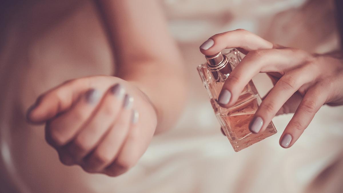 O femeie care poartă o rochie crem își aplică parfum pe mâini