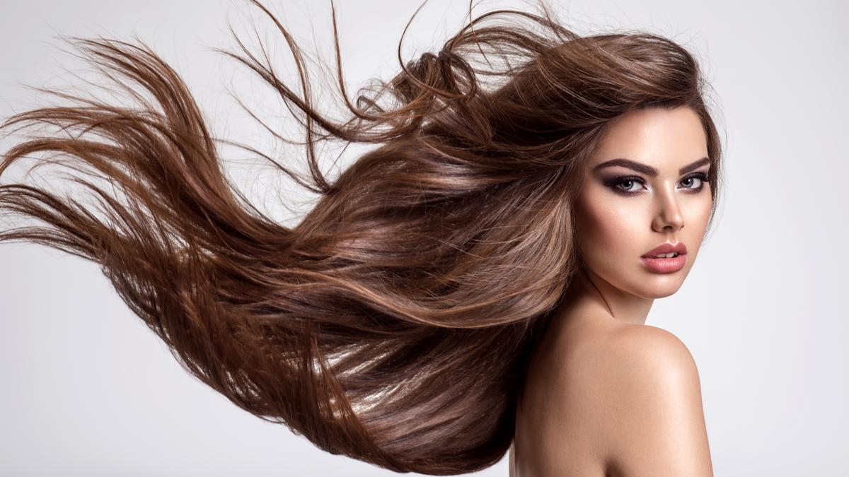 O fată pozează cu părul lung ridicat de vânt