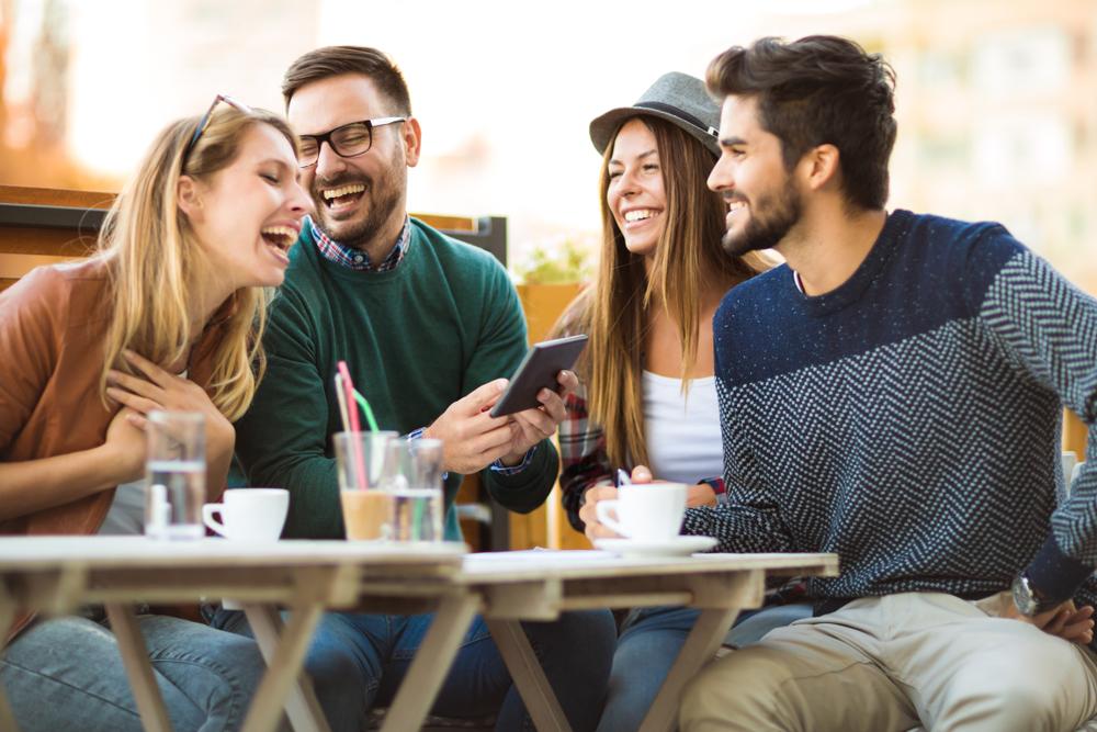 Un grup de patru prieteni care beau cafea împreună și râd, iar unul dintre ei ține în mână o tabletă