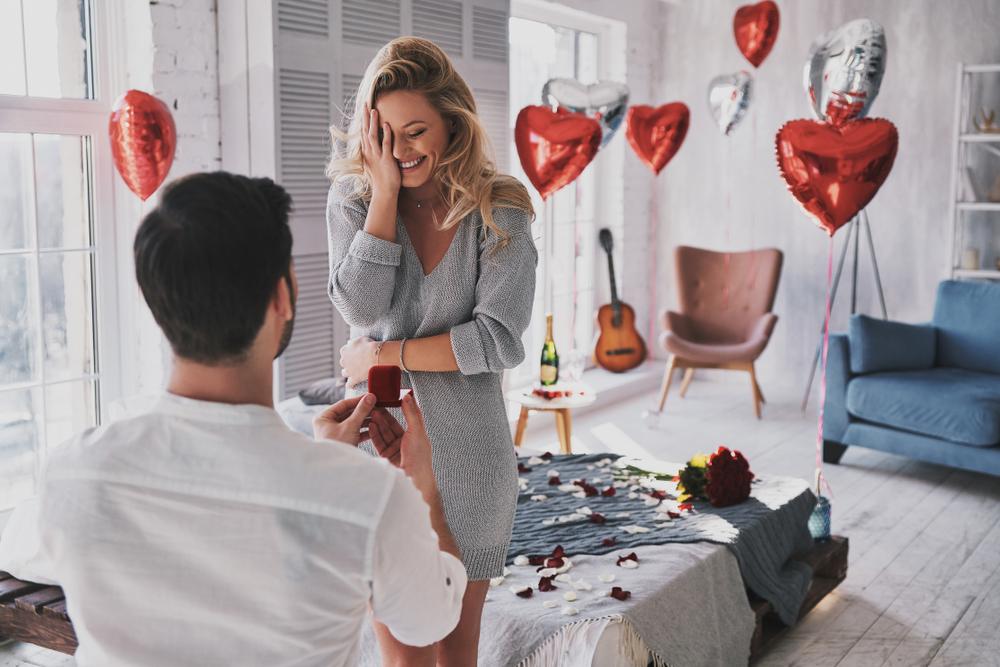 O femeie tânără este surprinsă și își acoperă fața cu mâna și zâmbește în timp ce iubitul ei o cere în căsătorie în genunchi