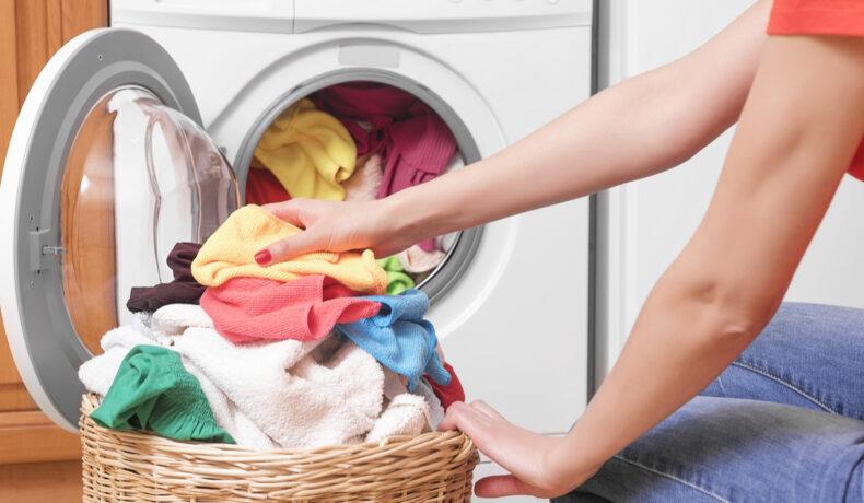 O femeie mută un mrman de haine coorate din coșul de rufe din lemn î mașina de spălat