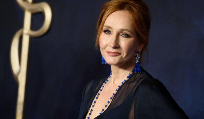 J. K. Rowling pozează pe covorul roșu îmbrăcată într-o rochie albastră, cu mărgele albastre la gât și cercei albaștri la urechi