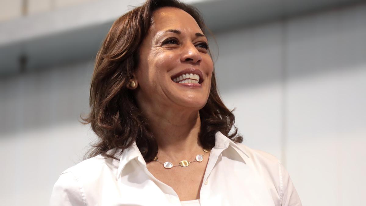 Kamala Harris zâmbește larg și este îmbrăcată cu o cămașă albă și poartă un colier alb la gât