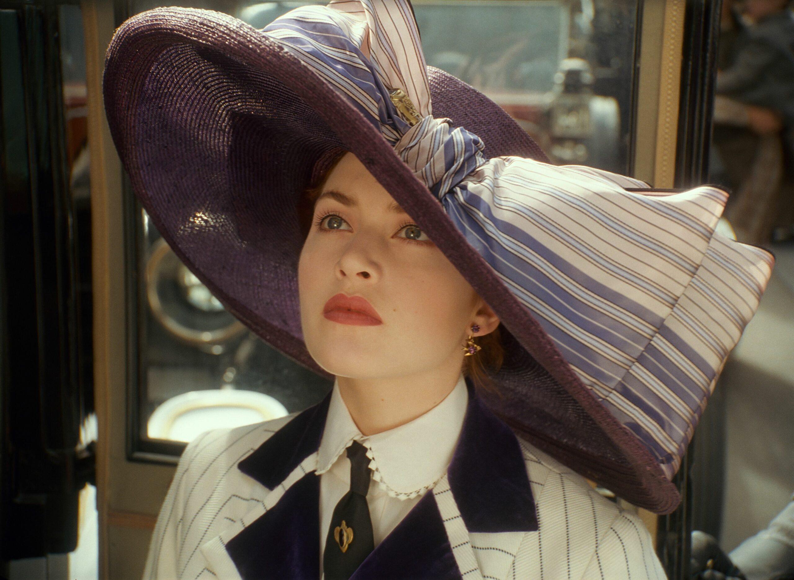 Kate Winslet poartă o pălărie mov cu o fundă mare într-o scenă din Titanic