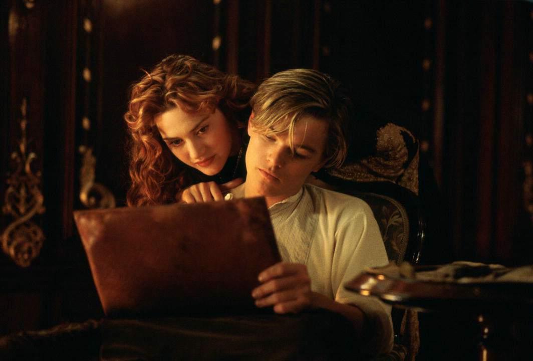 Leonardo Di Caprio îmbrăcat înr-o cămașă albă schițează un desen pe o planșă în timp ce Kate Winslet îl privește cu capul așezat pe umărul lui.
