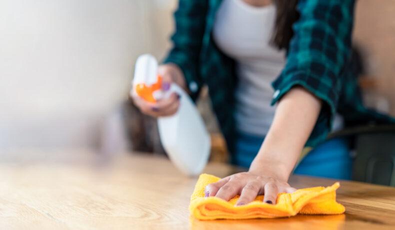 O femeie îmbrăcată într-o cămașă verde unul dintre cele mai murdare obiecte din casă cu o cârpă portocalie, iar în cealaltă mână ține un dezinfectant.