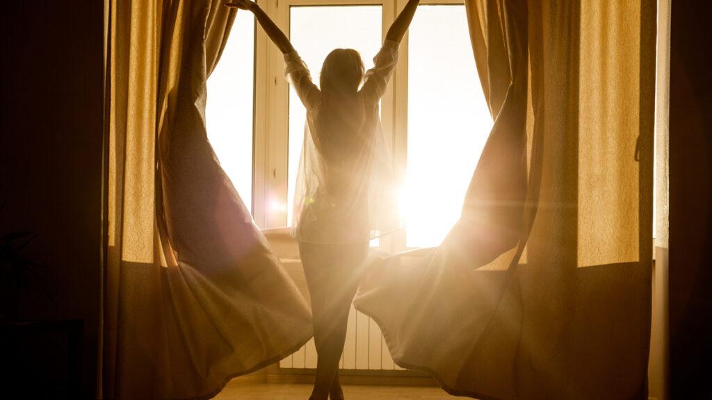 O femeie îmbrăcată cu o cămașă albă stă cu mâinile întinse în fața unei ferestre luminate de soare
