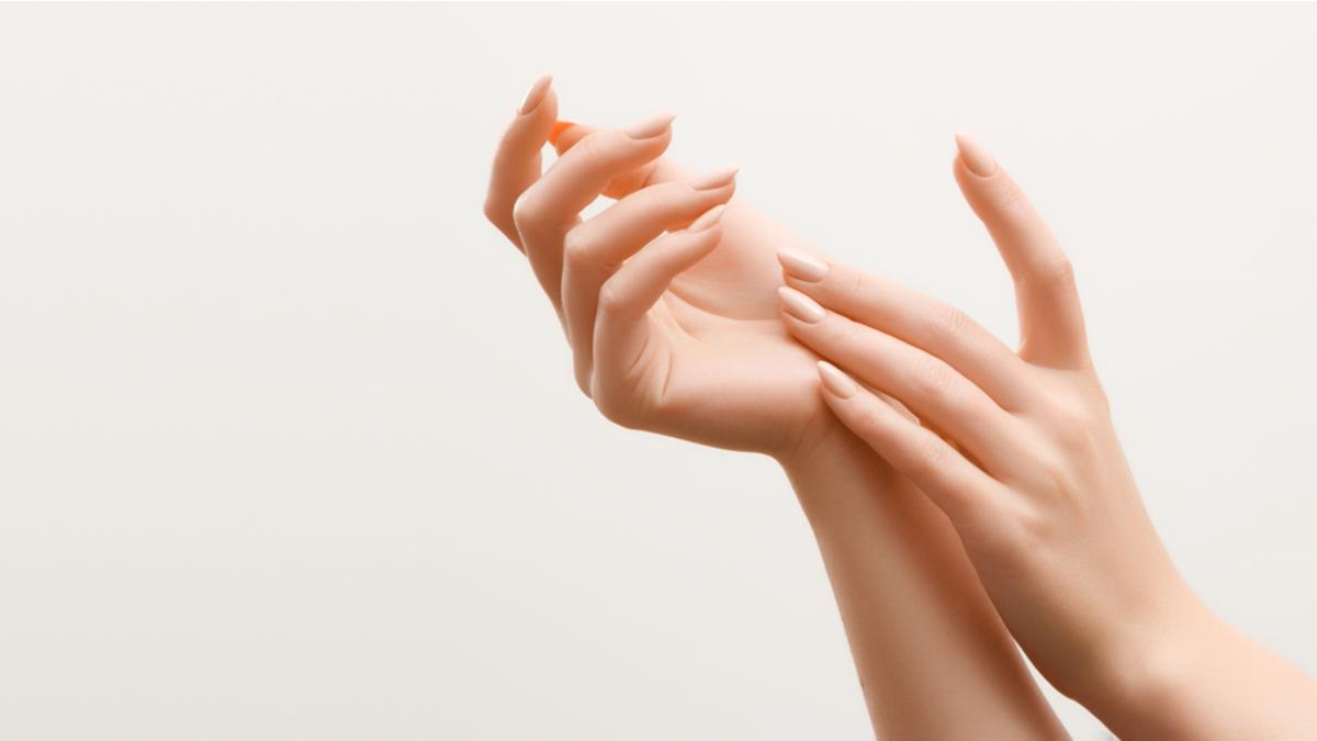 Două mâini subțiri de femeie cu manichiură de culoare bej