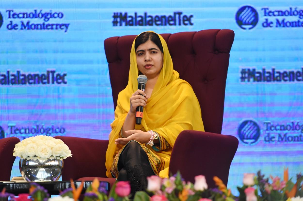 Malala este îmbrăcată într-un sari galben și stă așezată pe un fotoliu roșu în timpul unei conferințe