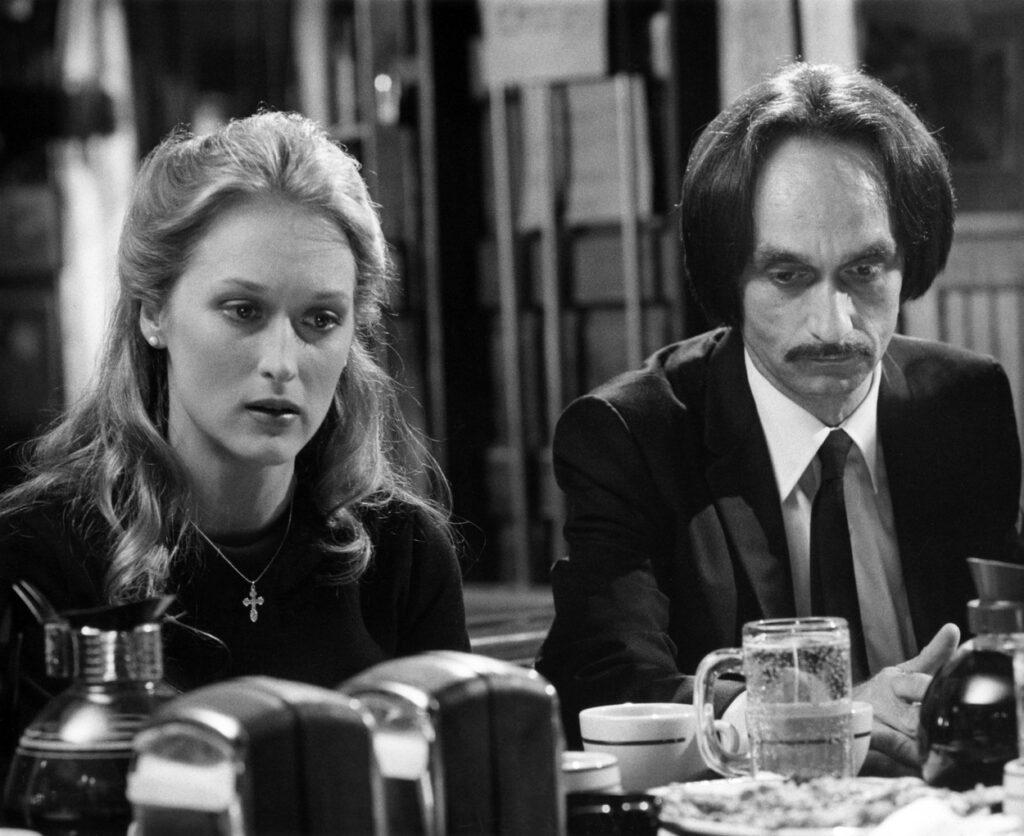 Fotografie alb-negru în care Meryl Streep stă așezată la masă alături de John Cazale