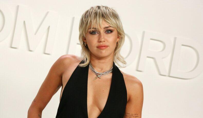 Miley Cyrus pozează îmbrăcată într-o rochi neagră cu decolteu adânc și o tusoare tip chică pe covorul roșu la prezentarea de modă Tom Ford