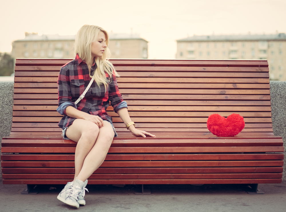 O femeie blondă care stă pe o bancă privește o pernă în formă de inimă așezată în celălalt capăt al băncii