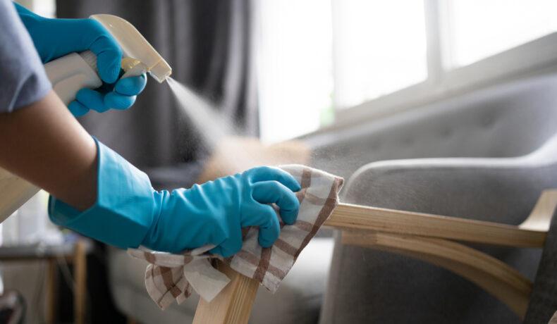 Două mâini care poartă mănuși albastre pentru curățenie șterg cu o cârpă și un produs de curățare mânerul unui fotoliu