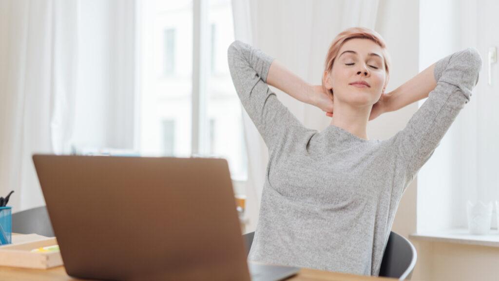 O femeie îmbrăcată cu o bluză gri își sprijnă capul în brațele rdicate la spate în timp ce stă așezată pe scaunul din fața biroului de lucru.