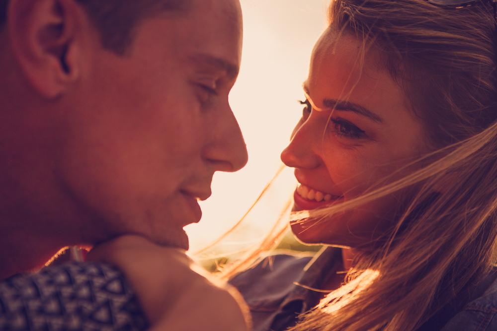 O femei își privește bărbatul iubit și îi zâmbește