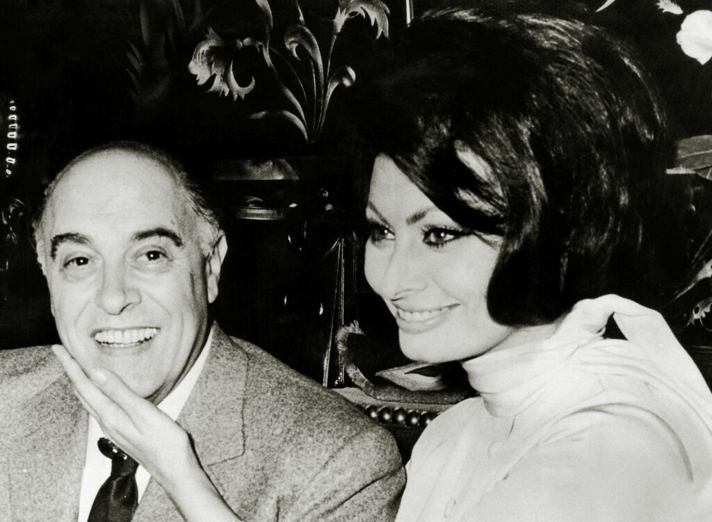 Fotografie alb-negru cu Sophia Loren care îl mângâie pe față pe soțul ei Carlo Ponti