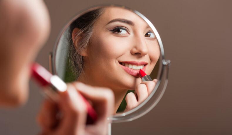 O femeie se uită în oglindă în timp ce aplică ruj roșu pe buze
