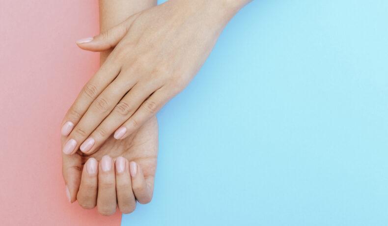 Două mâini cu manichiură transparentă pe un fundal albastru și roz