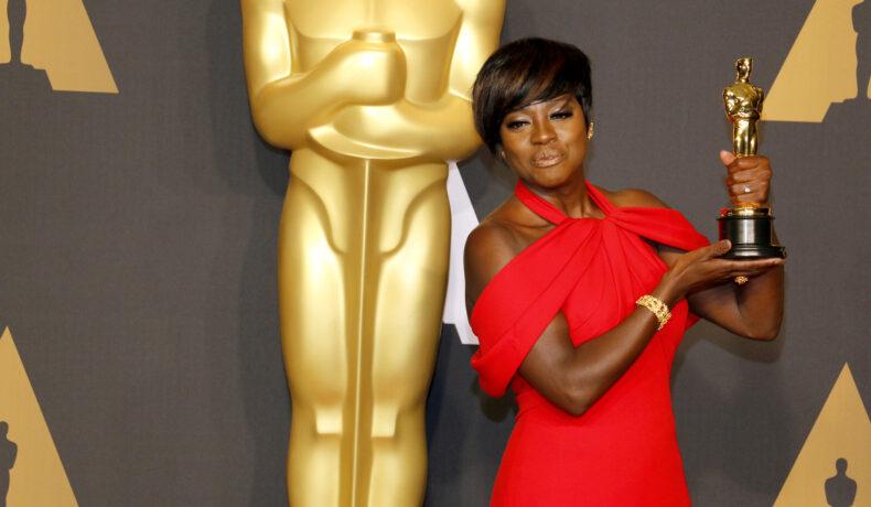 Viola Davis îmbrăcată într-o rochie roșie țină în mână o statuetă Oscar