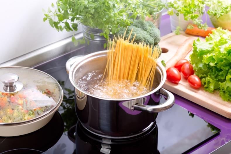 O oală pe foc, în care se fierb spaghette