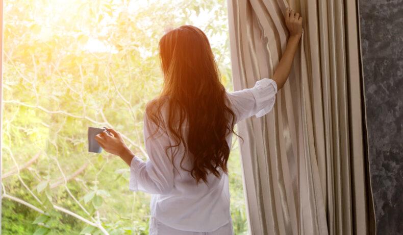 O femeie îmbrăcată cu o cămașă albă care ține în mână o cană înlătură perdeaua din dreptul geamului pentru a lăsa lumina să pătrundă în cameră