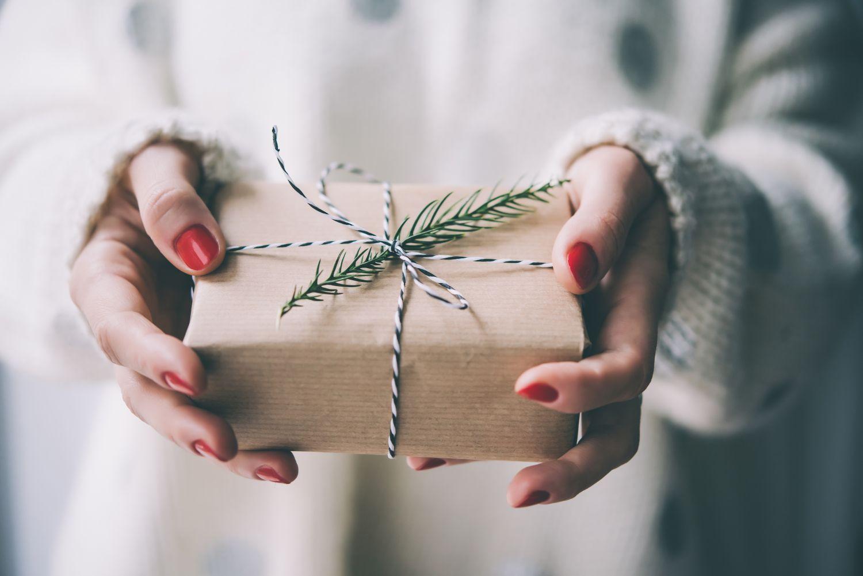 O femeie ține în mână un cadou de Crăciun potrivit în funcție de zodie.