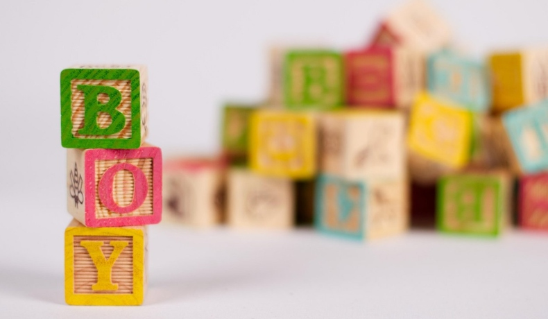 Cuburi colorate, cu inscripția Boy, așezate pe verticală, cu fundal alb, în spate