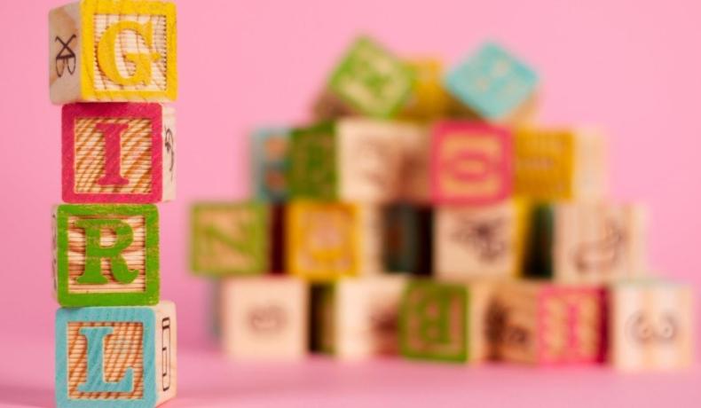 """Cuburi colorate, cu inscripția """"Girl"""", așezate pe verticală, cu fundal roz în spate"""